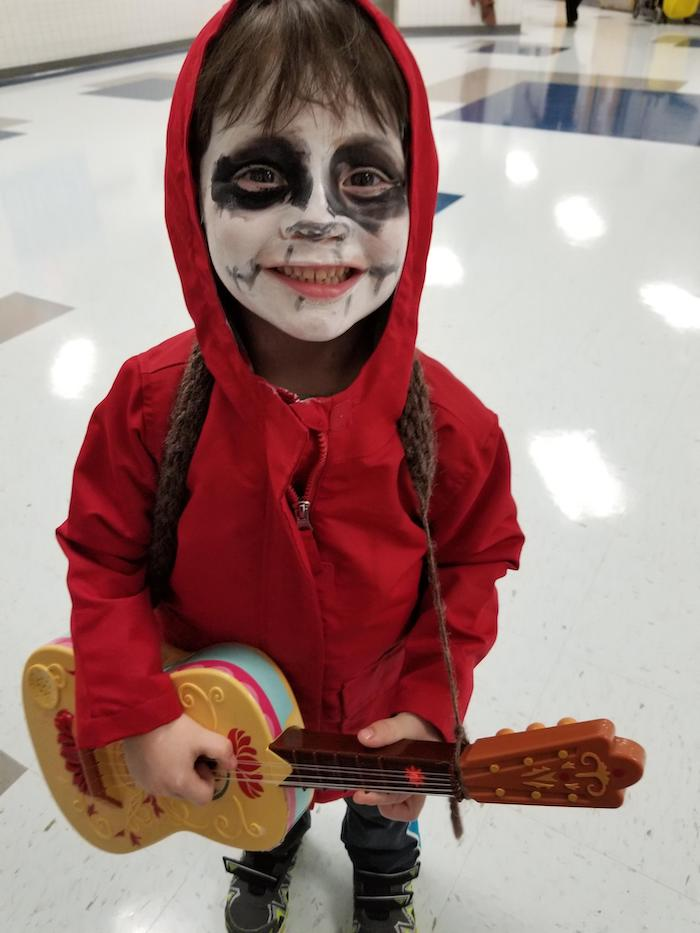little boy, dressed as miguel rivera, coco movie inspired costume, halloween costumes for girls, holding a guitar, red hoodie