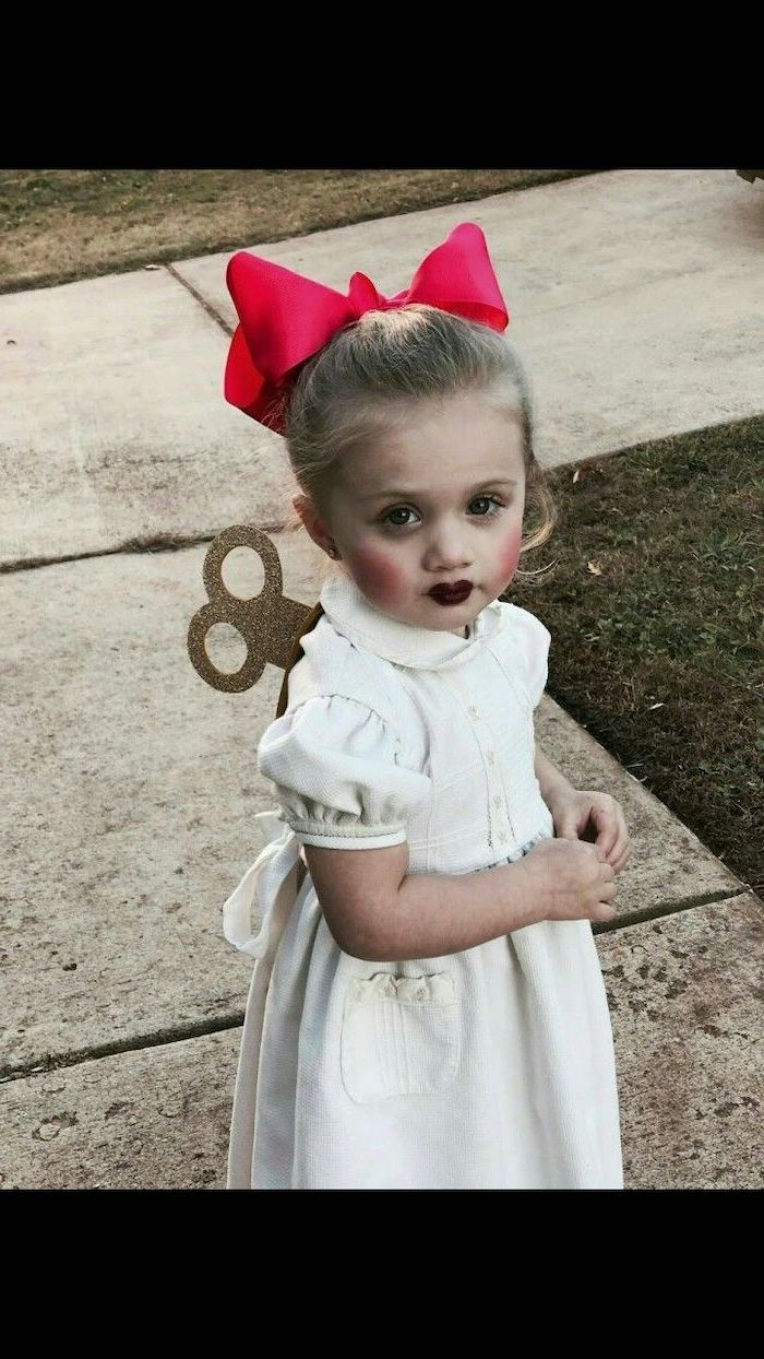 little girl, with blonde hair, dressed as a doll, wearing white dress, red bow, halloween costume ideas for girls