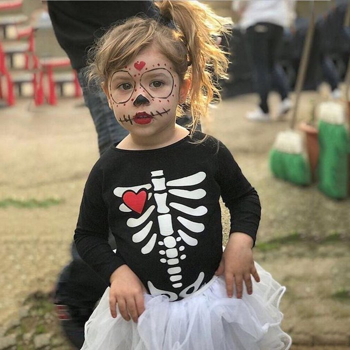 little girl, with blonde hair, dressed as skeleton, toddler boy halloween costumes, black shirt, calavera makeup
