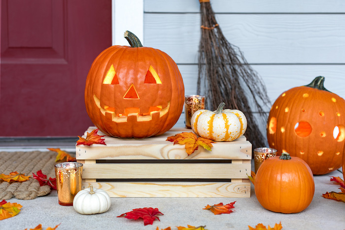 orange pumpkins, with different carvings, pumpkin carving, small pumpkins, arranged around a wooden crate