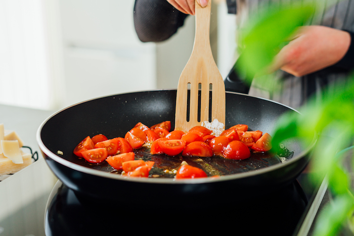 halved cherry tomatoes being cooked with chopped garlic in saucepan how to make zoodles with wooden spatula