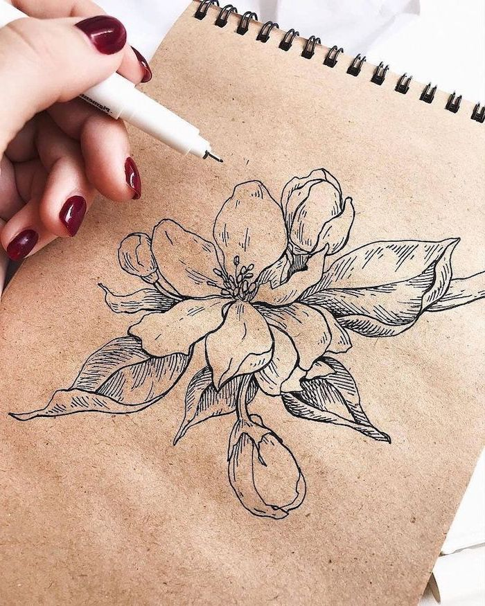 hand with red nail polish, holding a pencil, drawing a flower, simple drawing ideas