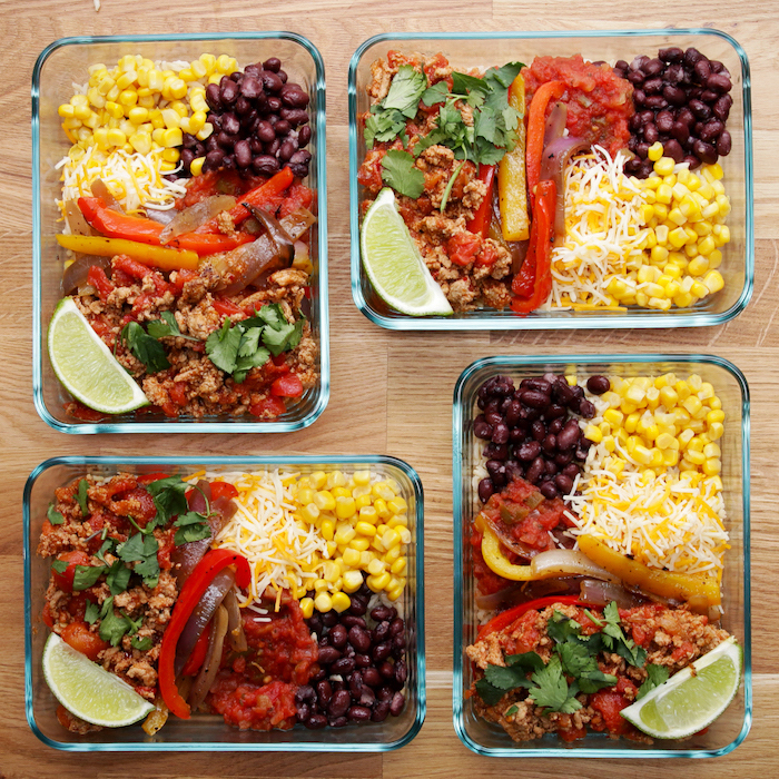 meal prep for the week, four glass containers, filled with corn and cheese, peppers and meat, black beans