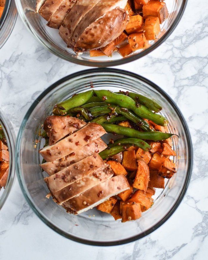 glass bowl, filled with marinated chicken, sesame seeds, beans and sweet potato, meal prep for the week, marble countertop