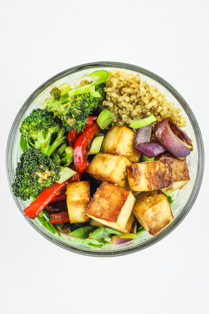 glass bowl, filled with quinoa, healthy lunch ideas for work, broccoli and peppers, tofu salad