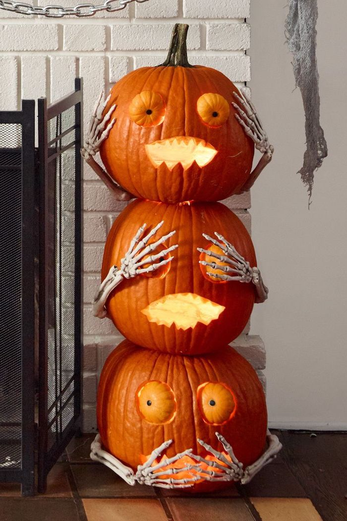hear see say no evil, three pumpkins, stacked together, with skeleton hands, pumpkin carving, white brick wall