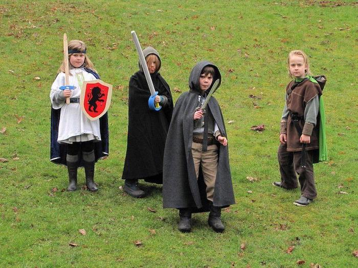 four boys, dressed as hobbits, halloween costume ideas for girls, hobbit inspired, standing on a grass field