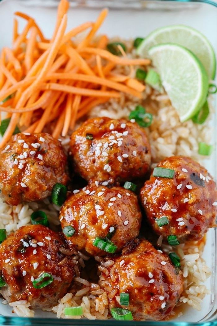 healthy lunch recipes, honey sriracha meatballs, rice and carrots, lime slices, in a glass container