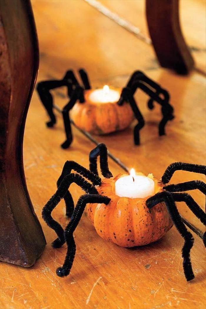 two small pumpkins, with candles inside, spider legs, glued to them, pumpkin faces ideas, wooden floor
