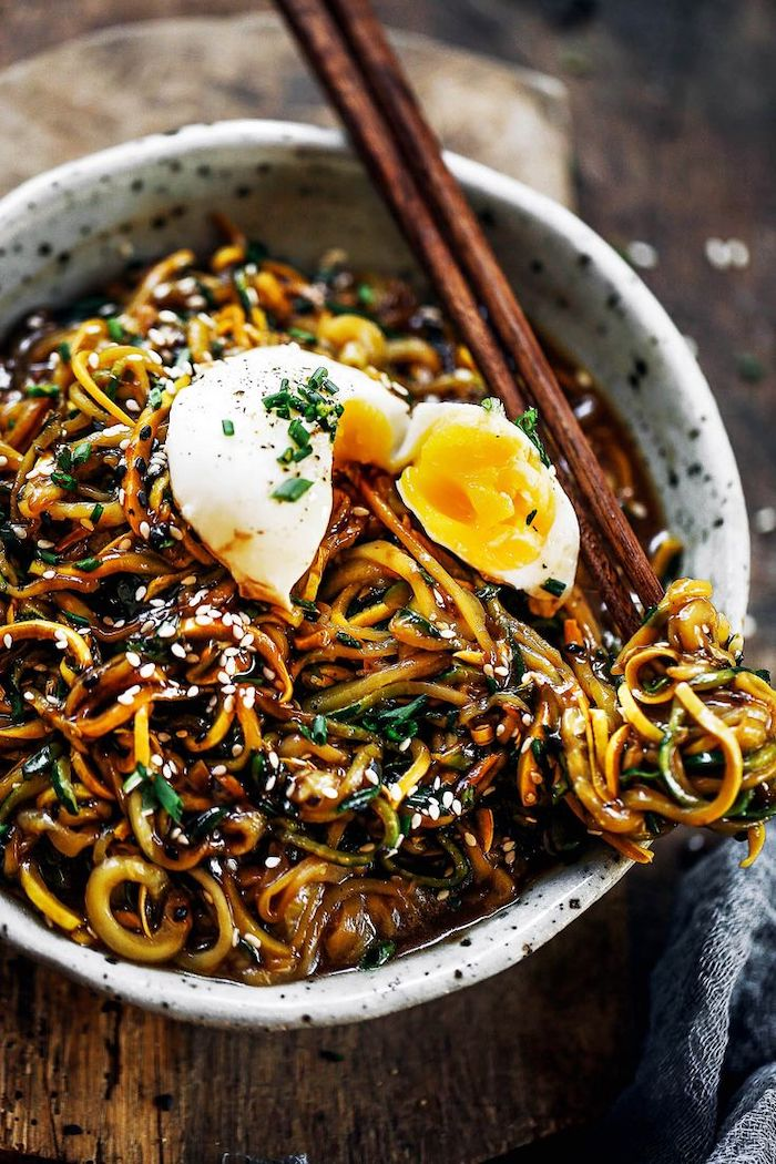 zucchini noodles, asian recipe, with sesame seeds, egg on top, in a white bowl, with wooden chopsticks
