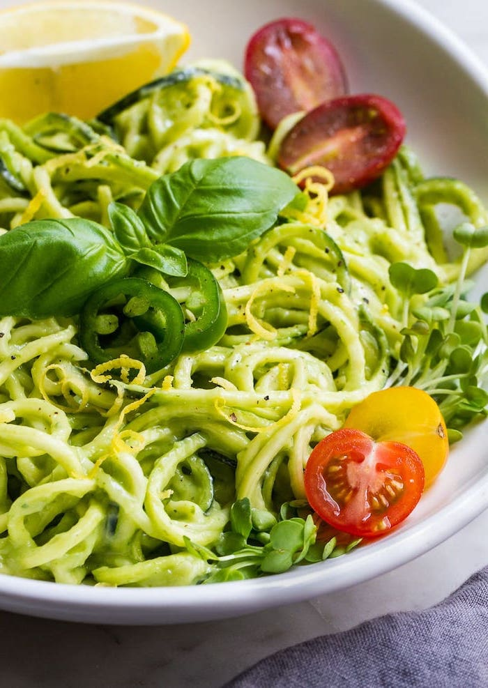 how to spiralize zucchini, cherry tomatoes, chopped peppers, basil on top, zoodles in white plate