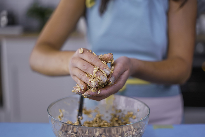 woman shaping cookies, oatmeal cookies, chocolate chip cookies, mix in a glass bowl, wearing a blue apron