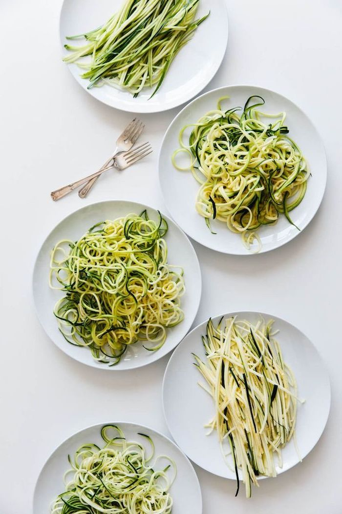 zoodles in five different ways, in white plates, on white table, how to spiralize zucchini, two forks