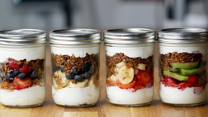 healthy lunch ideas for work, four mason jars, granola and yoghurt, different fruits inside, berries and bananas