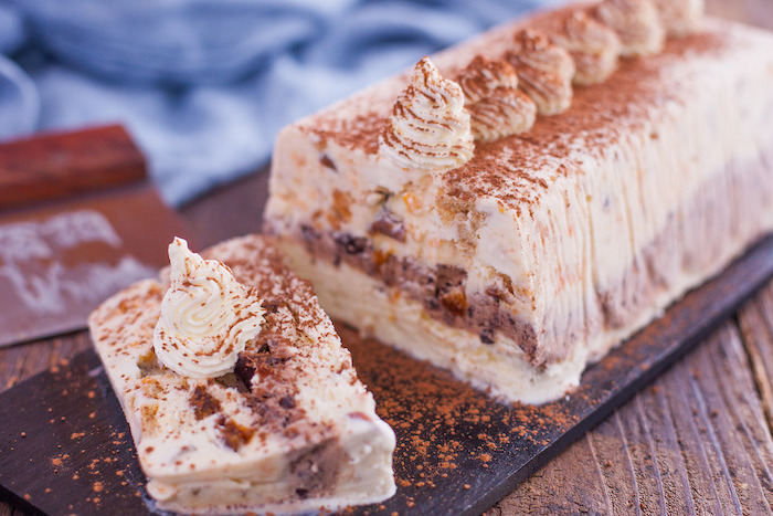 ice cream loaf, covered in cinnamon, on a black, cutting board, simple dessert recipes, wooden table