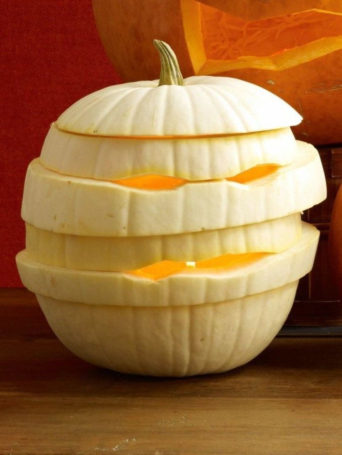 white pumpkin, carved and sliced, in the shape of a mummy, cute pumpkin carvings, wooden table