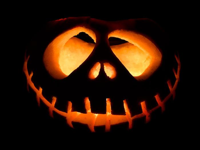 jack skellington, carved into a pumpkin, lit by candle, easy pumpkin carving, black background