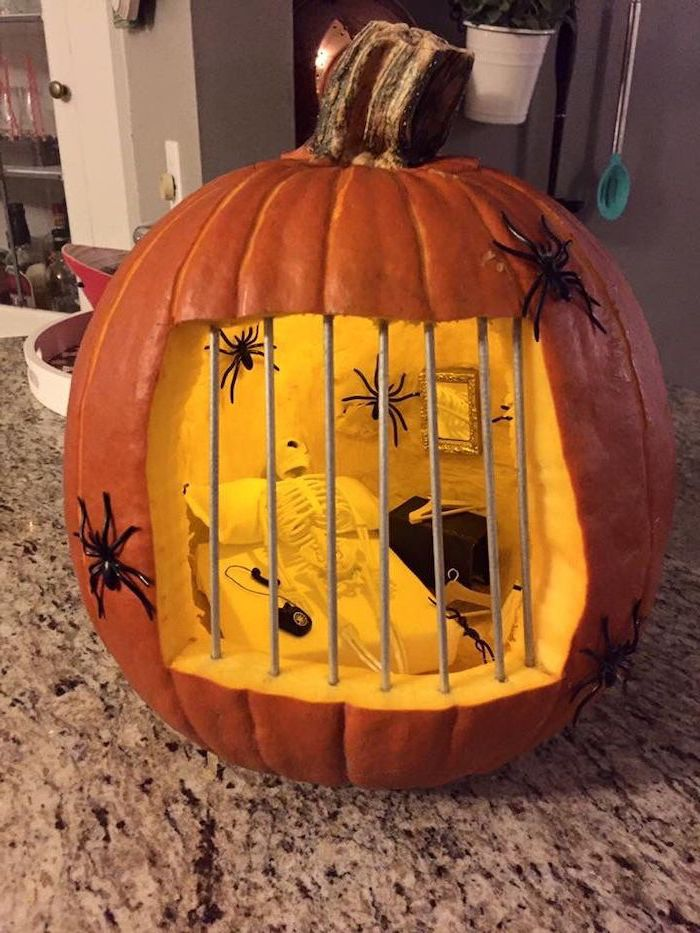 jail cell, skeleton inside, laying on a small bed, inside a pumpkin, cute pumpkin carvings, plastic spiders