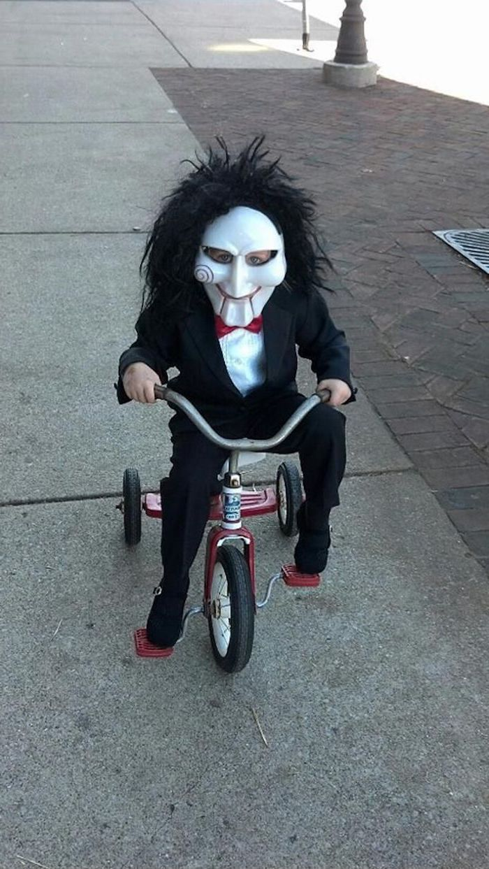 little boy, dressed as jigsaw, saw movie inspired, riding a tricycle, toddler boy halloween costumes, face mask