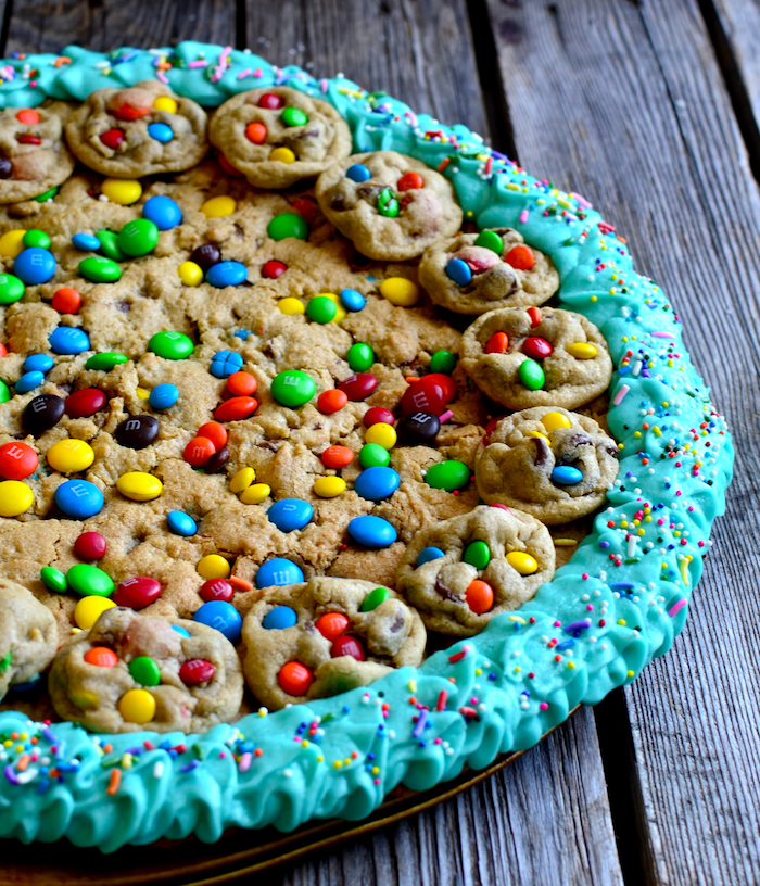cookie dough cake, with smaller cookies, with m and ms, blue frosting around, how to make homemade cookies, wooden table