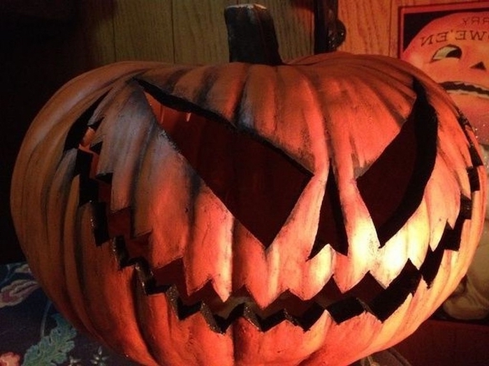 scary face, carved into a pumpkin, cute pumpkin carvings, wooden wall