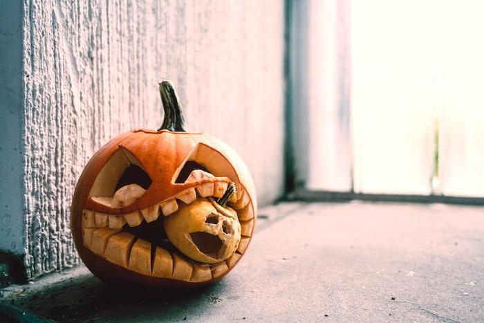 large pumpkin, eating a small pumpkin, pumpkin carving faces, cement floor, white wall