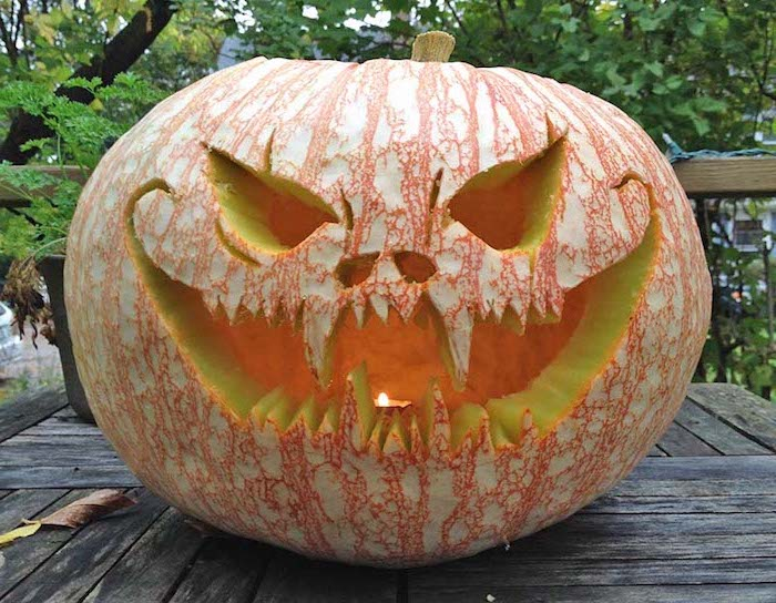 scary face, carved into a pumpkin, lit by a candle, easy pumpkin carving, wooden table, trees in the background