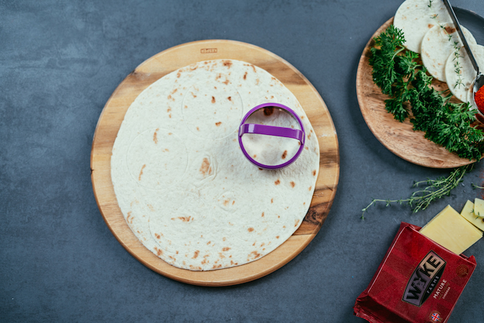 tortilla wrap, cut in smaller circles, on a wooden cutting board, on a black table, taco recipe, packet of cheese