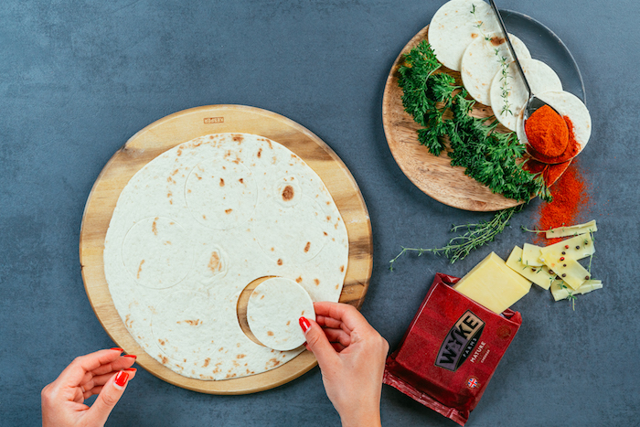 tortilla wrap, cut into smaller circles, on a wooden, cutting board, taco recipe, black table, packet of cheese