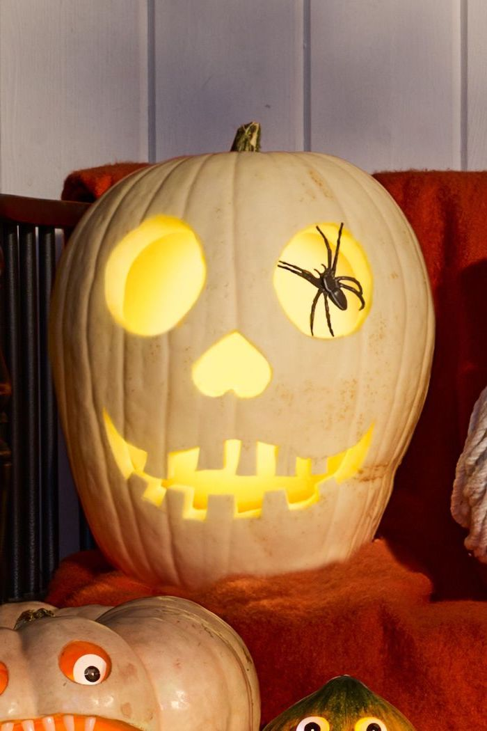 white pumpkin, pumpkin carving faces, plastic spider, inside the eye, pumpkin carving faces, orange blanket