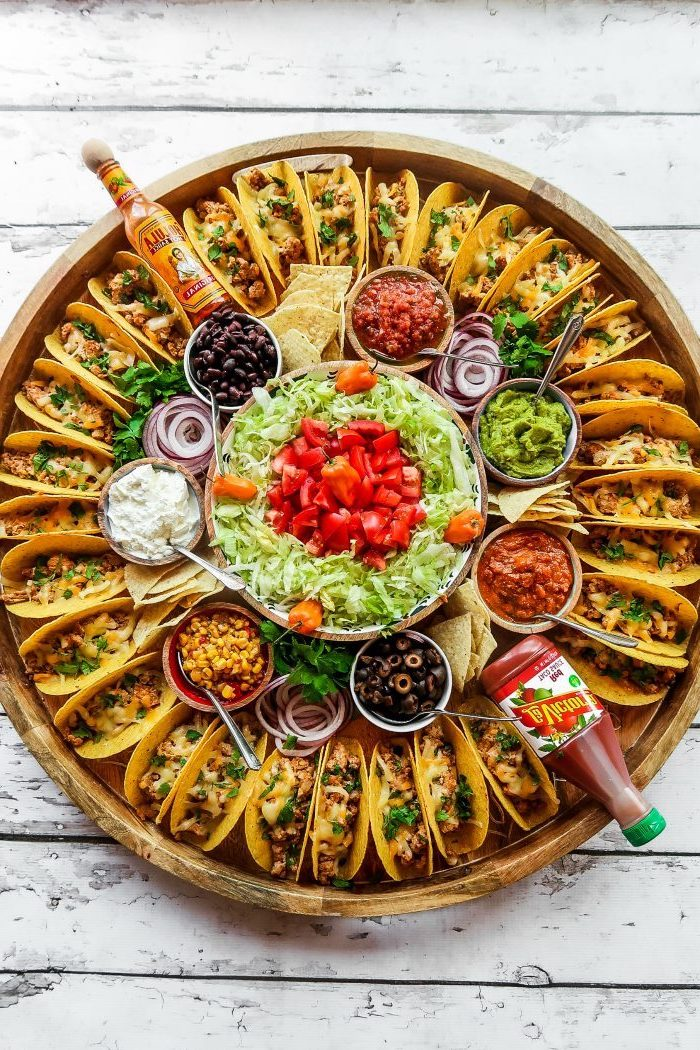 mini tacos, arranged on a large, wooden tray, glass bowls, filled with different ingredients, ground beef taco recipe