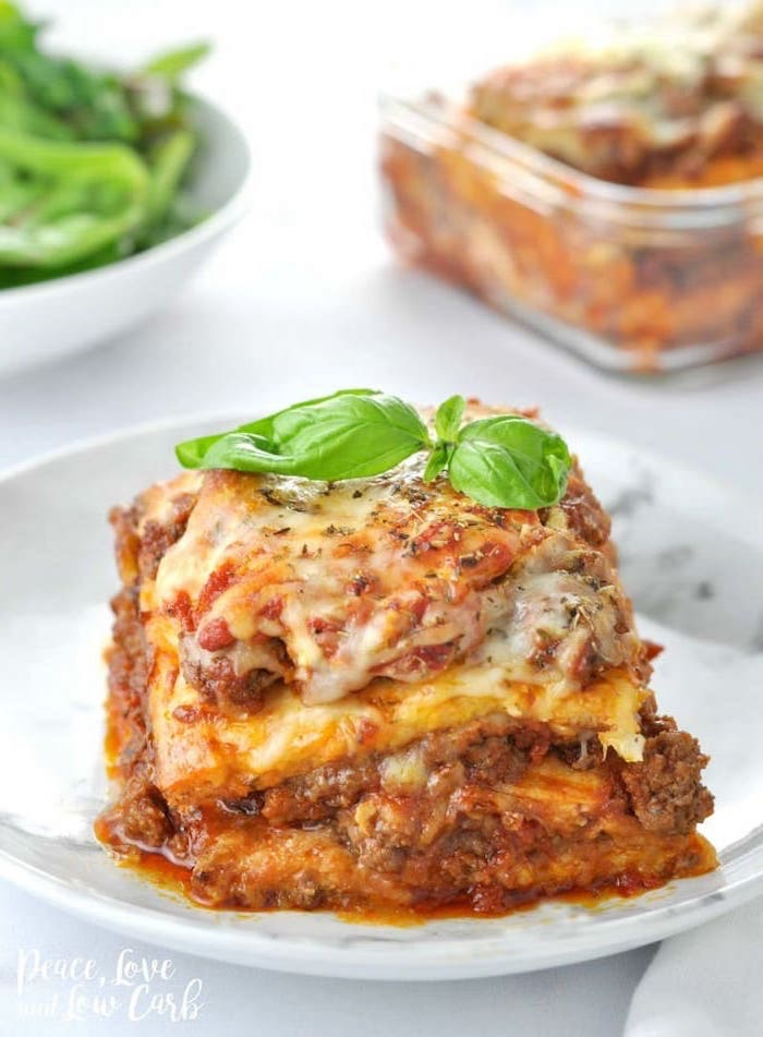 italian lasagna, with minced meat, cheese and tomato sauce, healthy lunch ideas for work, basil leaf on top