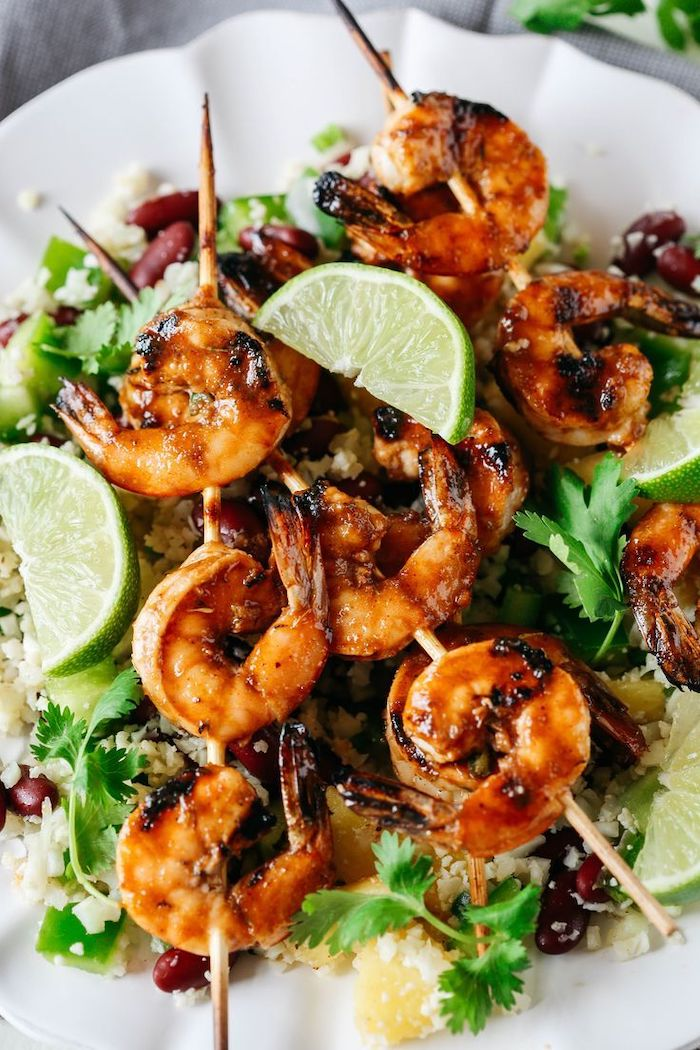 shrimp on wooden skewers, healthy lunch recipes, rise with black beans, lime slices, parsley on the side