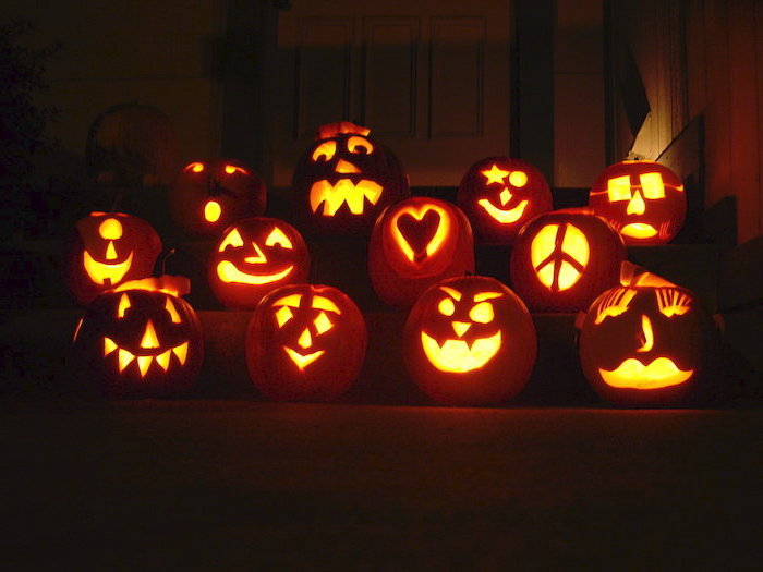 lot os pumpkins, lit by candles, arranged on a staircase, pumpkin carving faces