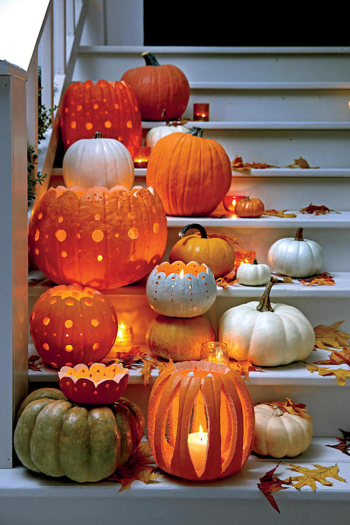 lots of pumpkins, lit by candles, arranged on white, wooden staircase, easy pumpkin carving
