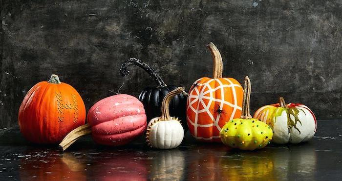 different shaped pumpkins, painted in different colors, easy pumpkin carving, black background, halloween pumpkin faces to carve