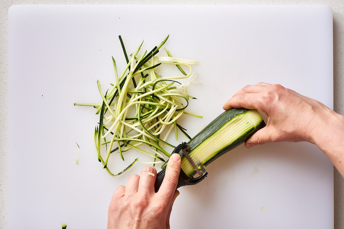 making zucchini noodles, with julienne peeler, white cutting board, how to make zoodles