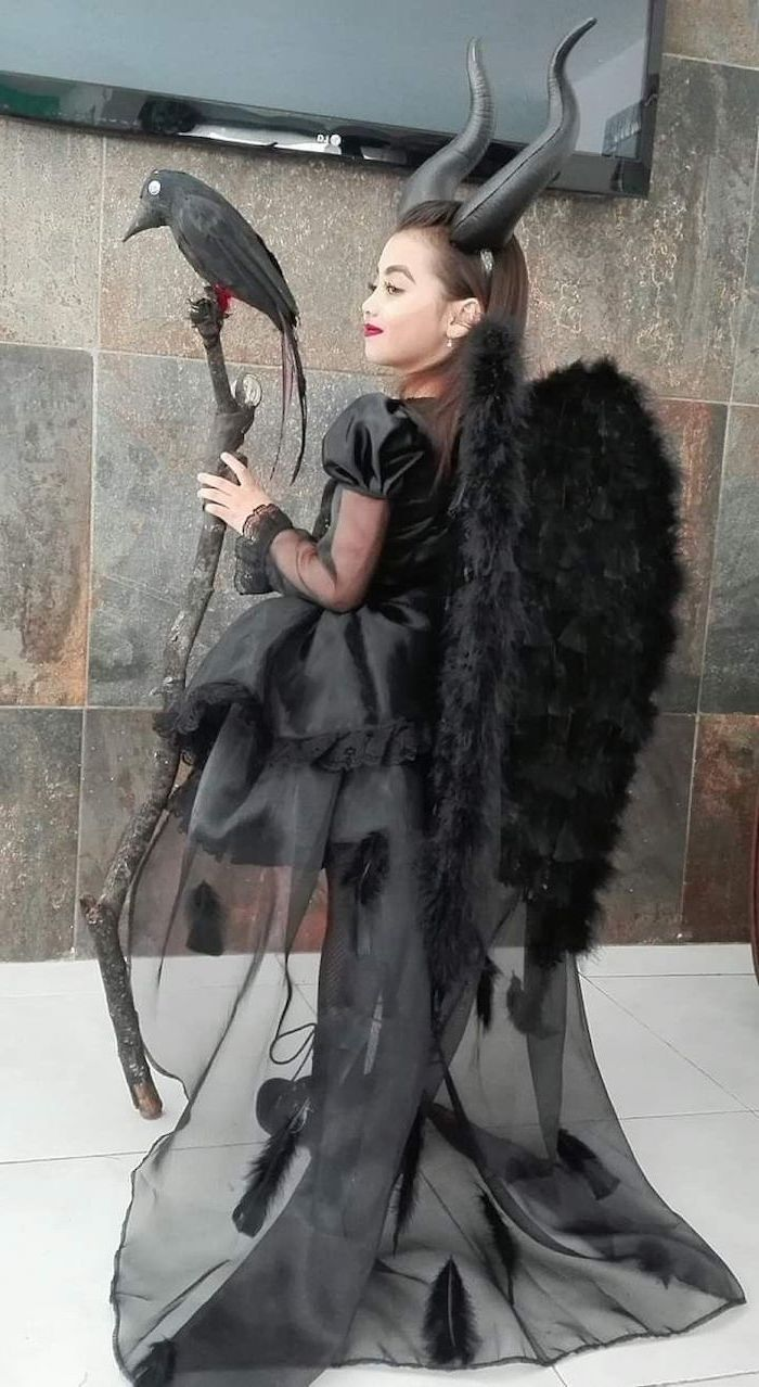 girl dressed as maleficent, furry wings, tulle skirt, satin gown, funny kids costumes, holding a staff with a bird