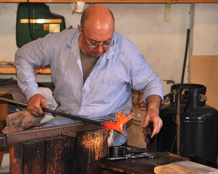 man making glass, wearing glasses, blue shirt, wooden table, different tools, murano glass chandelier