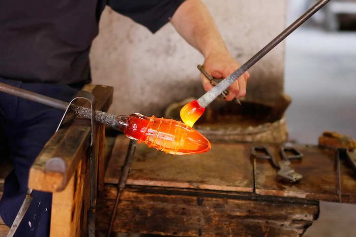 man holding tools, on wooden table, molten glass, murano glass chandelier, man with black shirt