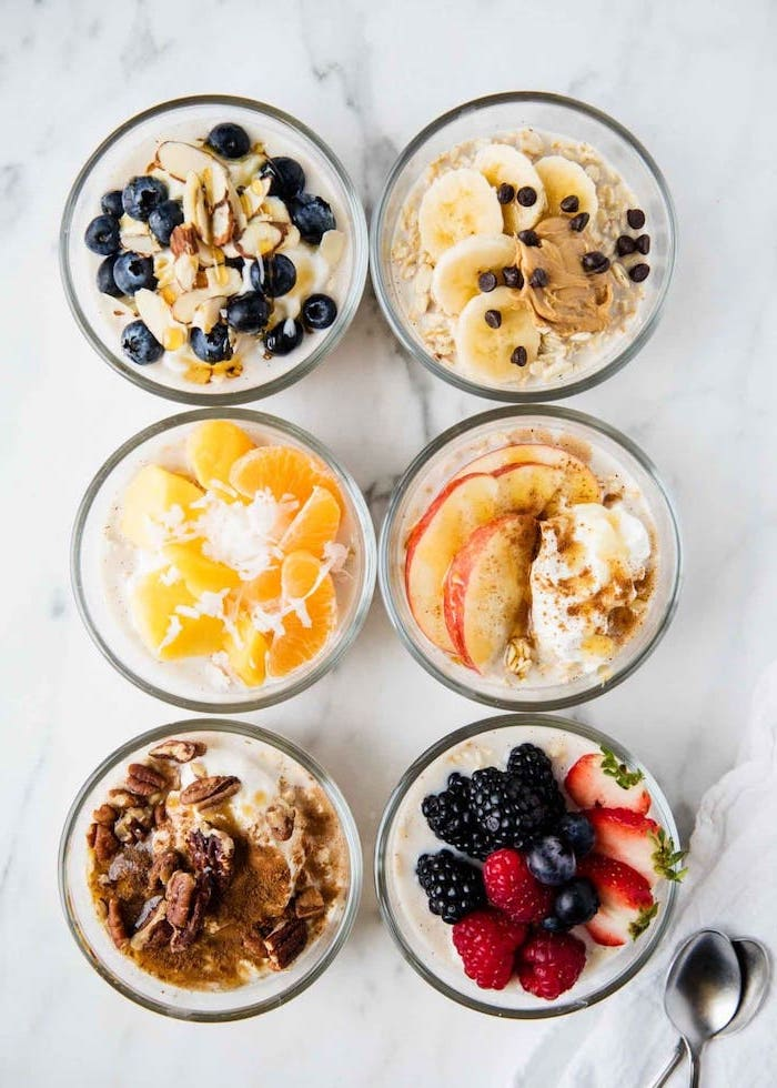 six glass bowls, filled with oatmeal, berries and bananas, apples and nuts, healthy lunch ideas for work, silver spoons