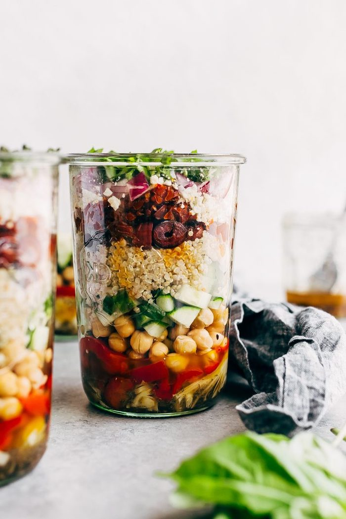 greek quinoa salad, inside a mason jar, meal prep for weight loss, with chickpeas and cucumbers, black beans