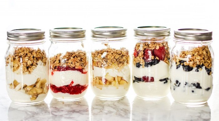 five mason jars, filled with fruits, granola and yoghurt, meal prep, white background, berries and bananas