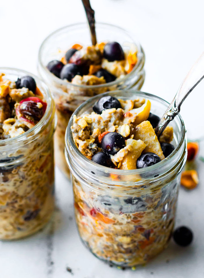 granola and yoghurt, berries inside a mason jar, with silver spoon, easy lunches for work, white wooden table