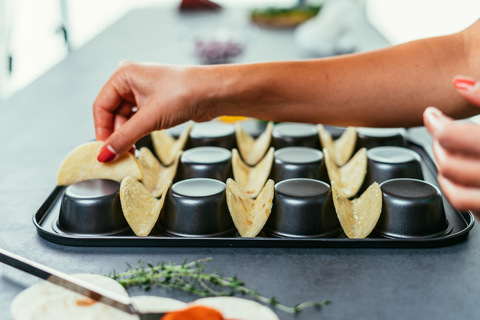 how to make tacos, tortilla wraps, arranged on a black, muffin tray, woman with red nail polish