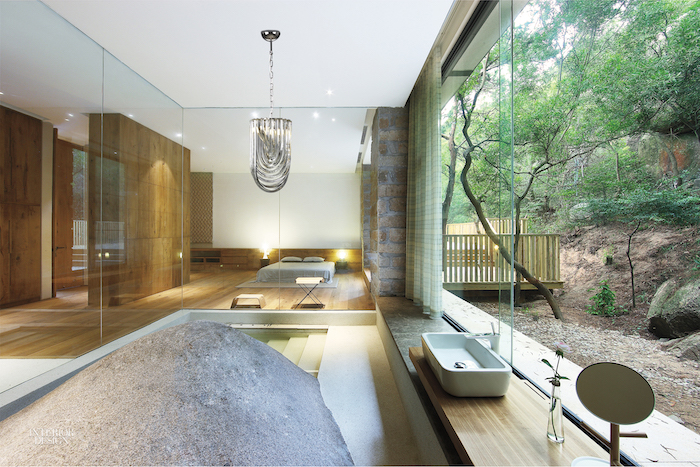 murano glass chandelier, sinking bath, separated with glass wall, from the bedroom, forest landscape