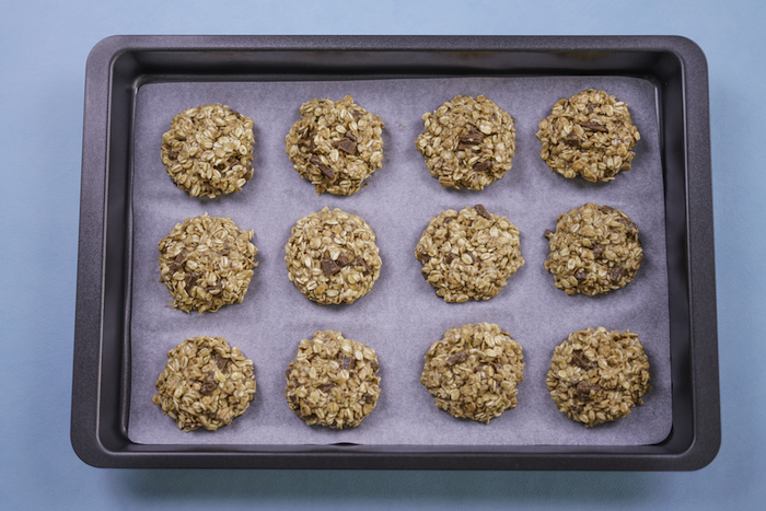 chocolate chip cookie recipe, oatmeal cookies, arranged on a white baking sheet, in a baking tray, blue table