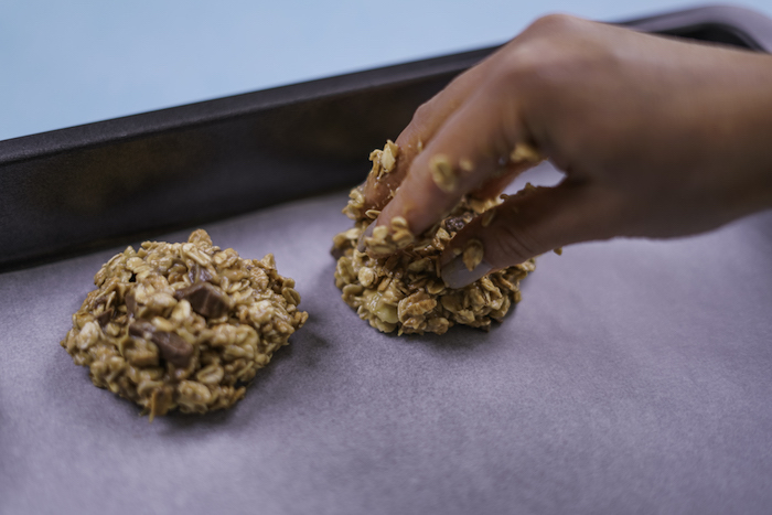 oatmeal cookies, tasty chocolate chip cookie, white baking paper, in a baking tray, blue table