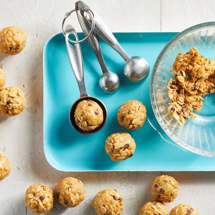 blue tray, measuring spoons, oatmeal mix, in a glass bowl, tasty chocolate chip cookie, wooden table