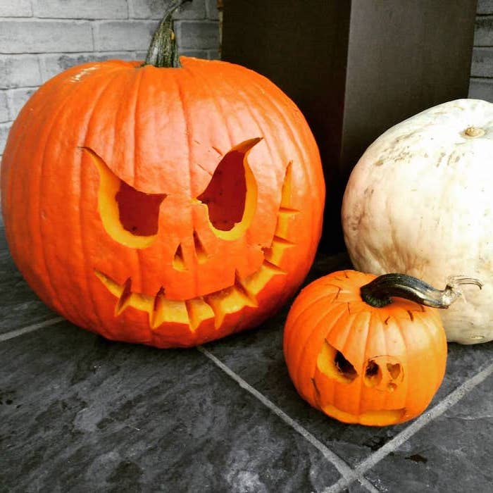 scary pumpkin carvings, large orange and white pumpkins, small orange pumpkin, tiled floor, brick wall